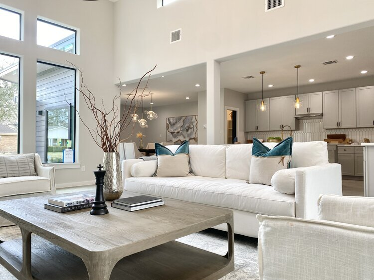 An all-white living room with a gray table, a white couch, and white pillows with blue accents.