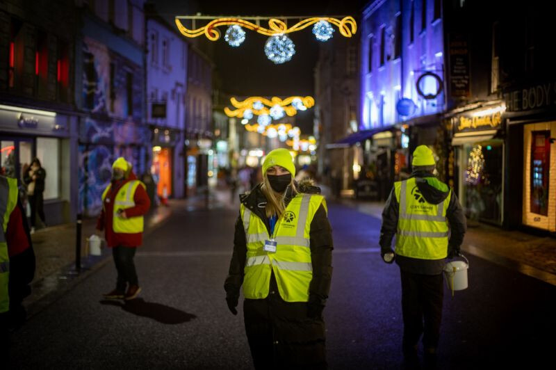 Wayfair employee Tamara McGough stands in a reflective yellow vest outside at night for COPE Galway's event.