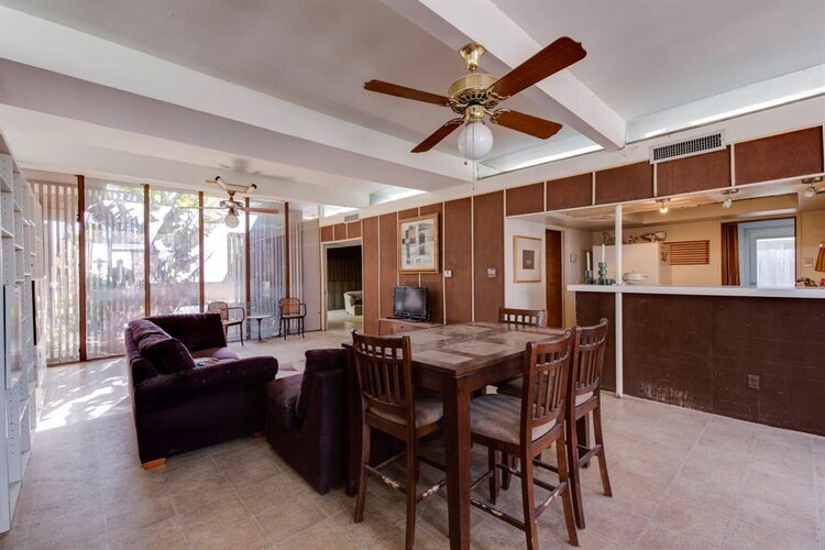 """A """"before"""" photo of the previous room, which is more sparse, and shows a brown kitchen island with brown stools."""