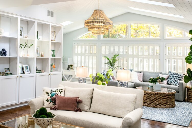 A hardwood floored living room with a white couch and a white bookshelf.