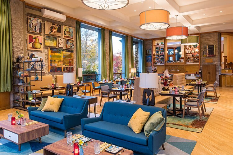 Two stylish blue couches sit in front of a large room with nicely spaced, small tables.