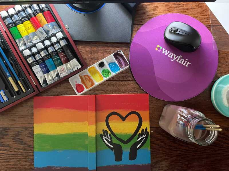 A table with a Wayfair mouse pad, paints, brushes, and a rainbow painting of two hands holding a heart.